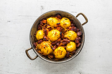 Potatoes. Roasted potatoes with bacon onion and sausages on white concrete table