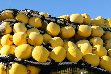 Industrial fishing net with large yellow floats over blue sky background