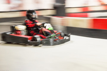 Fotomurales - Cart (kart) blurred by high speed, a boy having fun - driving fast, racing, speeding.