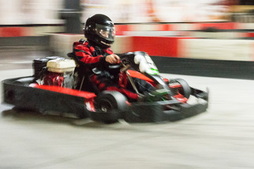 Cart (kart) blurred by high speed, a boy having fun - driving fast, racing, speeding.