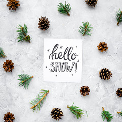Hello snow hand lettering. Winter pattern with pinecones and spruce branch on grey background top view
