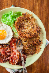 Hash browns. Potato pancakes with crispy fried bacon and fried e