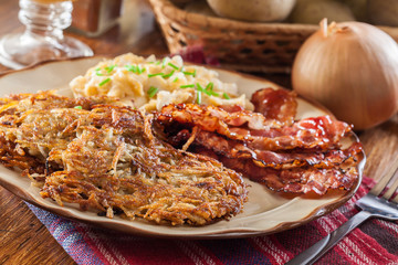 Hash browns. Potato pancakes with crispy fried bacon and scrambled eggs
