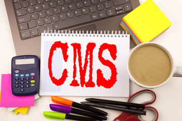 Word writing CMS in the office with laptop, marker, pen, stationery, coffee. Business concept for CMS WWW Workshop white background with copy space
