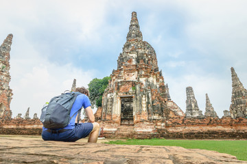 Tourist sit and wait at Wat Chaiwatthanaram of Ayutthaya Historical Park is Thailand ancient buddhist temple.