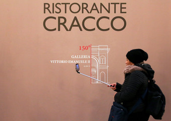 A women uses her mobile phone in front of Italian celebrity chef Carlo Cracco's next opening restaurant downtown Milan