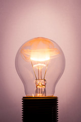 Vintage photo of bulb on light background with flame inside