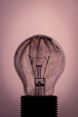 Vintage photo of bulb on light background with smoke inside
