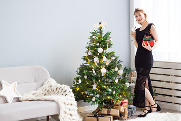 Young happy beautiful woman in black dress stands  with a glass of champagne  and  gifts in hands near Christmas tree. New Year celebration.