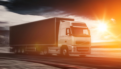 Large freight truck driving at sunset