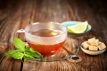 Hot cup of tea with brown sugar and lemon and mint leaves