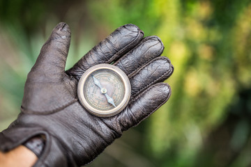 Man's hand in a leather glove holding a compass. Nature background.