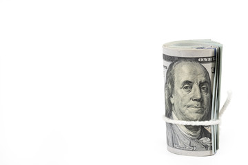 Roll of one hundred US dollar banknotes with white robe isolated on white background.