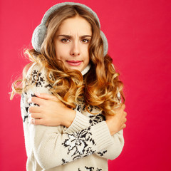 Young woman in winter sweather with knitted headphones over pink background
