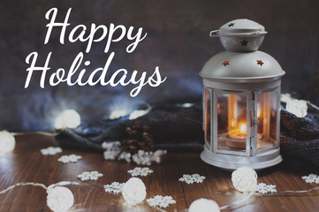 "Cozy winter home. Lantern, candle, garland, snowflakes, pine cone, knitted gray sweater on a wooden table. The atmosphere of a New Year's fairy tale. Text ""Happy Holidays""."