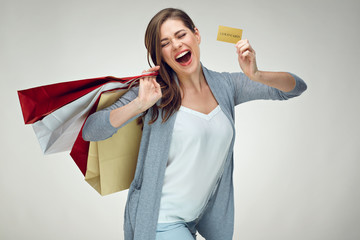 Happy emotional woman holding credit card and shopping bag.