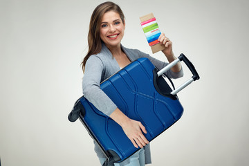 Smiling woman holding suitcase, tickets, passport.