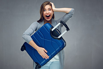 Surprising woman holding big suotcase ready for holiday.