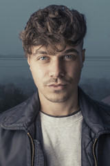 Fashion portrait photo of young and handsome man with curly hairstyle and leather jacket. Male model portrait with pretty look (posing  to camera). Photo of man with foggy and misty background.