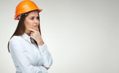 Portrait of thinking business woman wearing builder helmet isolated