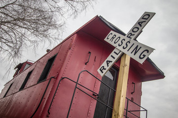 Railroad Crossing. Railroad crossing sign with historical red caboose.