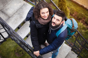 Top view, the couple is standing on the stairs, smiling and looking up.