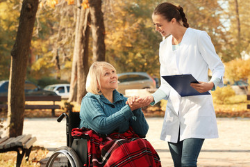 Disabled senior woman and young nurse in park