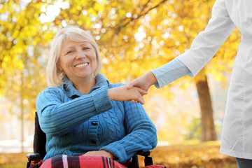 Disabled senior woman and young caregiver in park