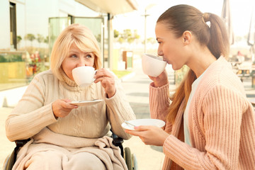 Disabled senior woman and young caregiver in outdoor cafe