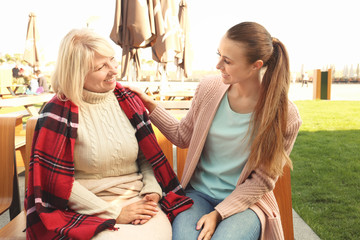 Senior woman and young caregiver sitting on bench in park