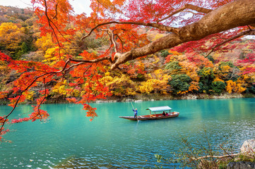 Poster Japan Boatman punting the boat at river. Arashiyama in autumn season along the river in Kyoto, Japan.