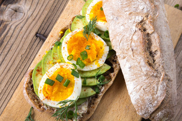 Avocado and egg sandwich on a wooden background. Fresh organic vegetables, eggs and whole wheat bread. Healthy breakfast. Rustic style.