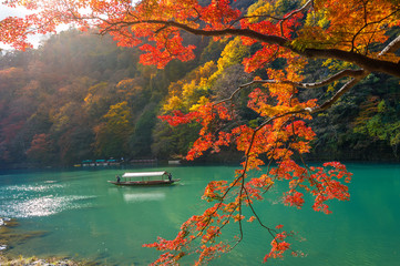Wall Mural - Boatman punting the boat at river. Arashiyama in autumn season along the river in Kyoto, Japan.