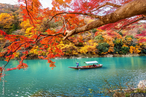Wall mural Boatman punting the boat at river. Arashiyama in autumn season along the river in Kyoto, Japan.