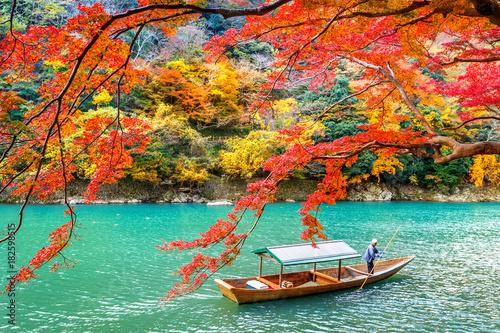Wall mural Boatman punting the boat at river. Arashiyama in autumn season along the river in Kyoto, Japan.
