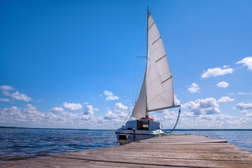 The yacht is near the pier. Blue sky and water. The concept of recreation and travel.