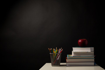 Back to School Concept, Stacked books, Colored Pencils and apple isolated on black background with place for your text