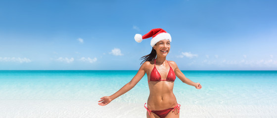 Wall Mural - Christmas bikini woman happy on tropical beach in Santa hat. Summer vacation banner with copy space. Asian girl with sexy body on blue sky and ocean water. Travel vacation holidays under the sun.