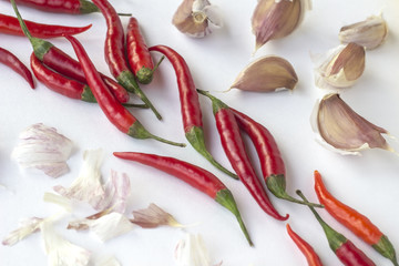 Red chili peppers and garlic cloves on a white background diagonally. Top view. Horizontally.