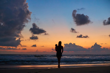 silhouette of mother carrying child in front of beautiful ocean beach sunset