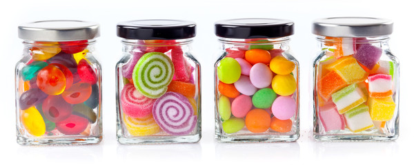 Zelfklevend Fotobehang Snoepjes colorful candies in glass jars on white background - Web banner with food concept