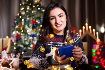Portrait of happy brunette woman holding a blue gift box in hands