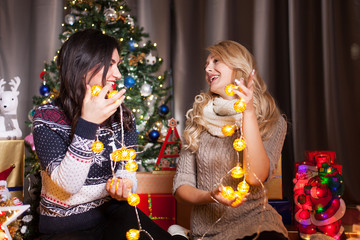 Two female friends next to a decorated christmas tree having fun