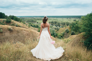 A young girl, the bride in a long wedding dress, is turned her back and stares into the distance to the river and a beautiful landscape.