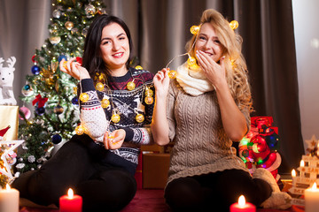 Happiness and friendship. Two women in christmas eve having fun in decorated house
