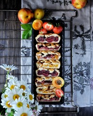 Patties with a lattice made of dough. Stuffing from strawberries, apricots, nectarines, peaches, cherries. On a grill