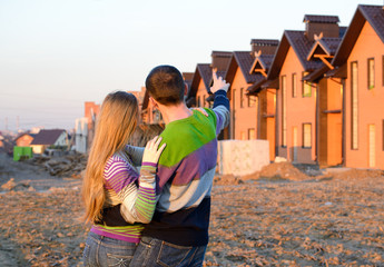 Rear view of young couple looking at their new house.