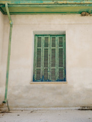 Old Cyprian window with green shutter and drainpipe.