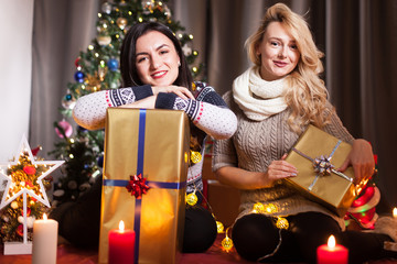 Sharing is caring. Happy girl friends exchange boxes with gifts in christmas decorated room