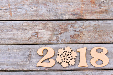 Number 2018 from wood and snowflake. On old rustic wooden background numbered 2018 from wooden and wood figure snowflake, copy space. New Year 2018 concept.
